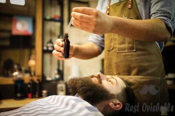 Barber putting beard oil to client What Is Beard Oil And The Ingredients Involved Within Beard Oil?