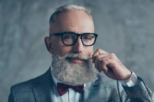 Close up portrait of grinning old-fashioned trendy elegant wealthy professional flirty trendsetter hipster grandpa sharp dressed with maroon bow-tie twisting white mustache isolated on grey background Beard Oil Smells Great