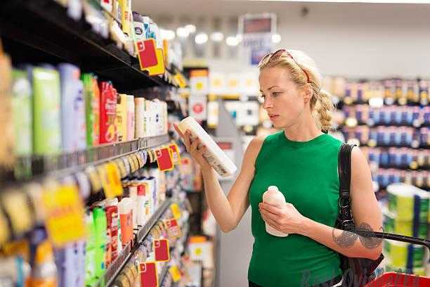 Woman shopping personal hygiene products at supermarket. shower gel vs body wash