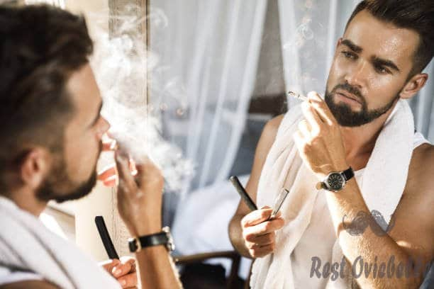 man looking in the mirror smoking a cigarette and shaving his beard with a straight razor - straight razor blades s and pictures best straight razor blades